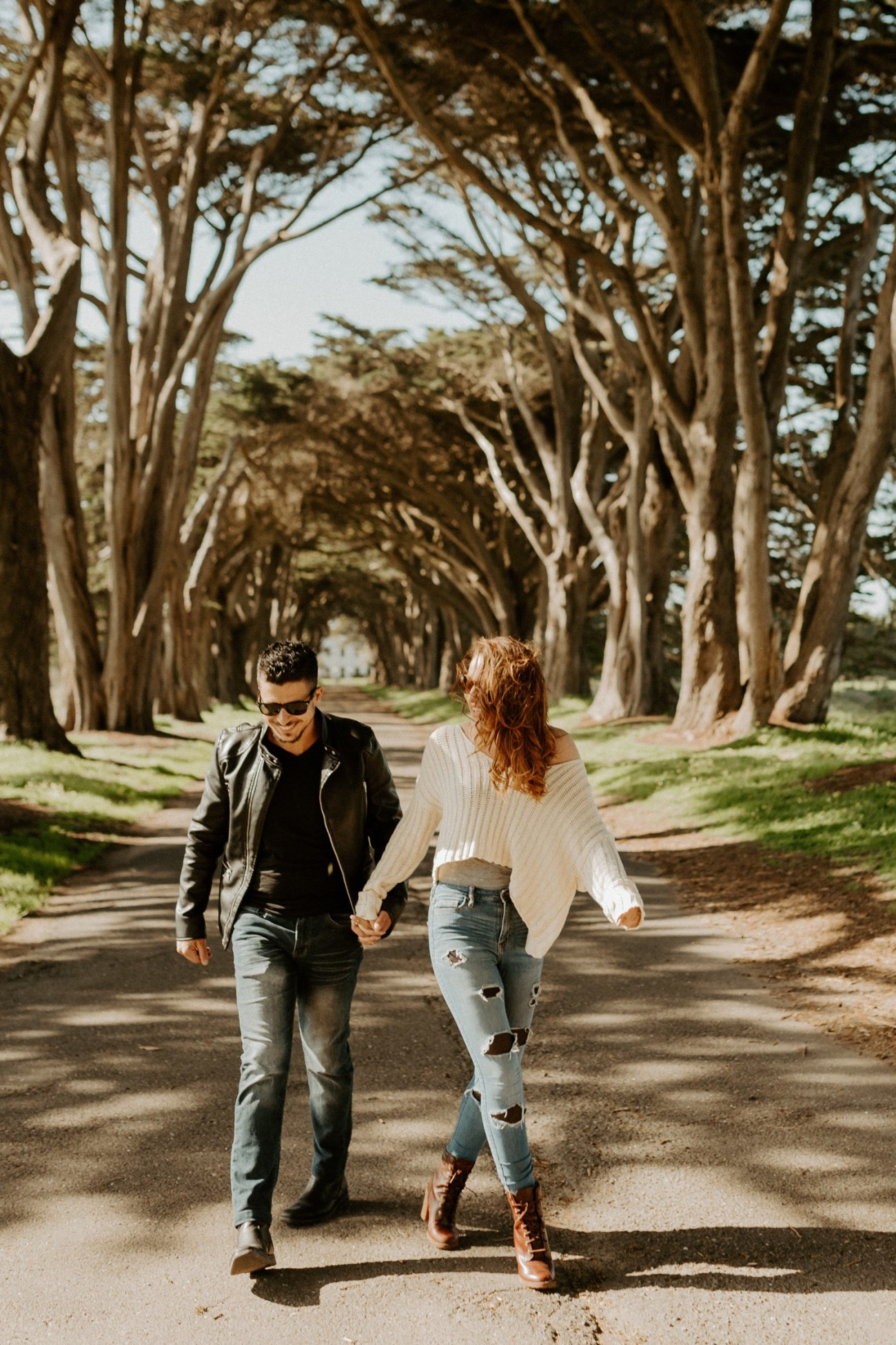 Couple walking through the Cypress Trees Tunnel in Point Reyes California for their Engagement Session