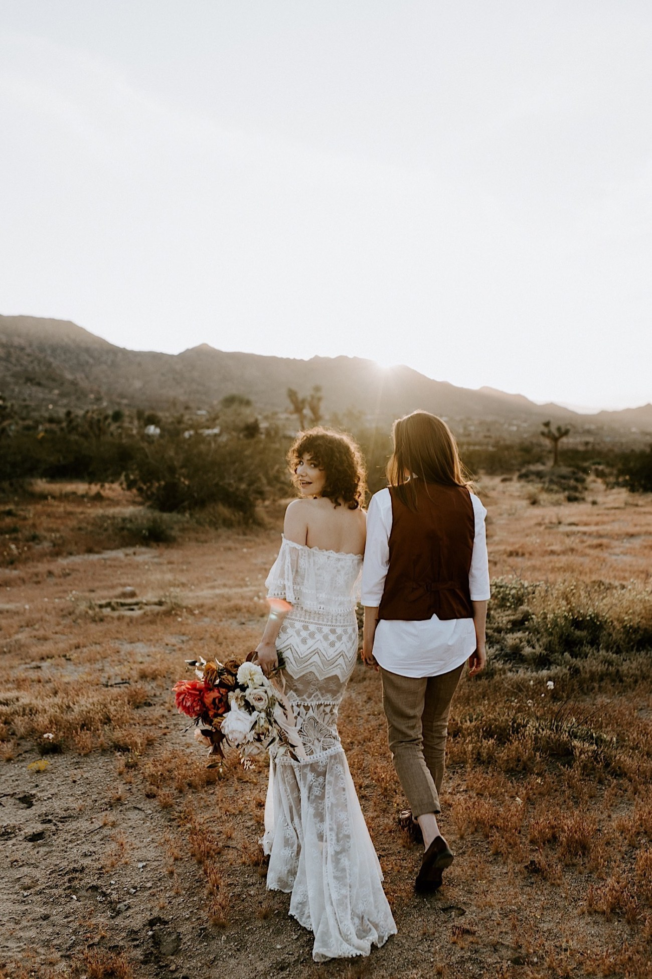 Same Sex Elopement in Joshua Tree, bride and bride standing next to a Joshua Tree. California Wedding Photographer.