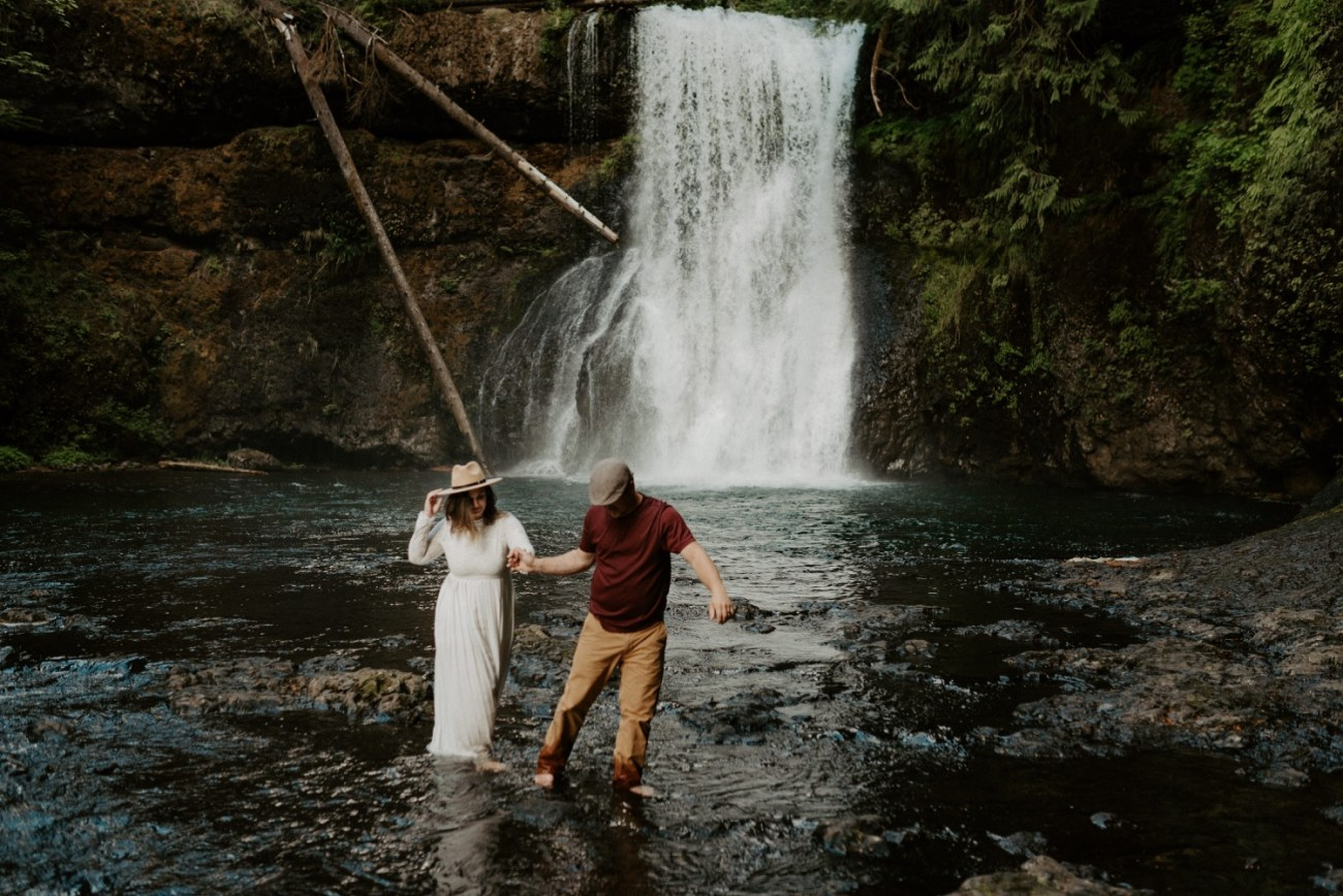 Couple walking by the Upper North Falls at Silver Falls State Park for their engagement photos. Anais Possamai Photography