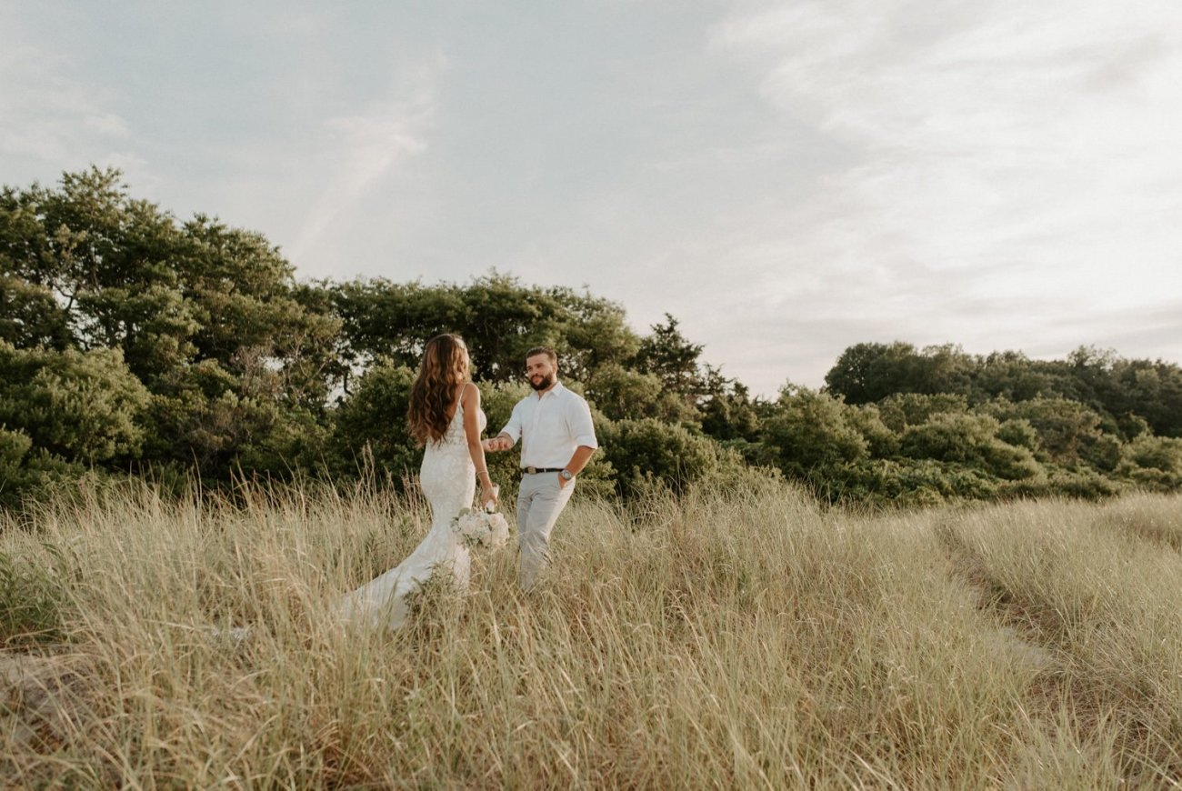 Bride and Groom walking on the beach at Sunken Meadow State Park in Long Island for their Wedding Bridal Portrait. New York Wedding Photographer. Anais Possamai Photography