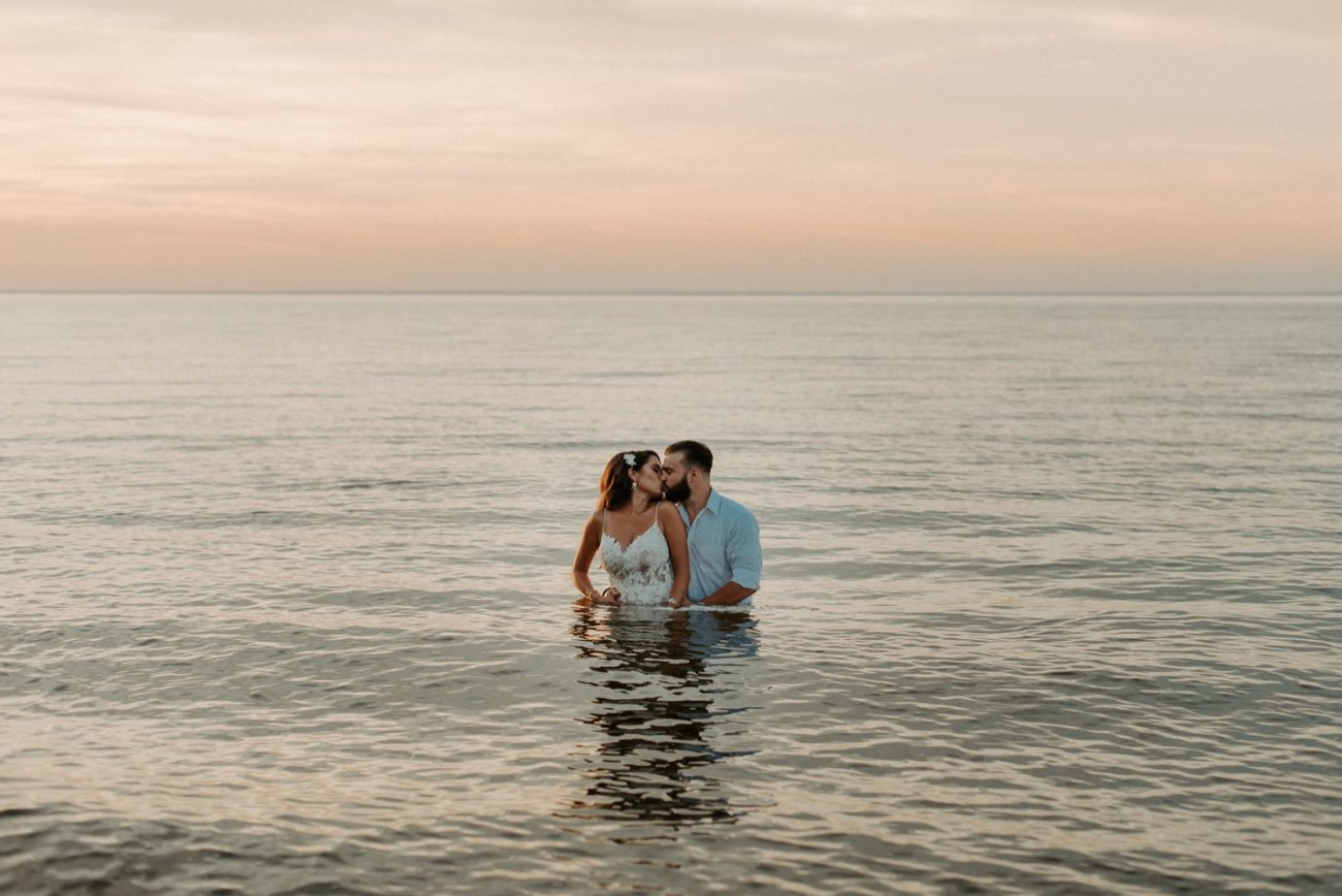 Bride and Groom standing in the water at Sunken Meadow State Park for their wedding bridal portrait. Fun trash the dress ideas. New York Wedding Photographer, Anais Possamai Photography