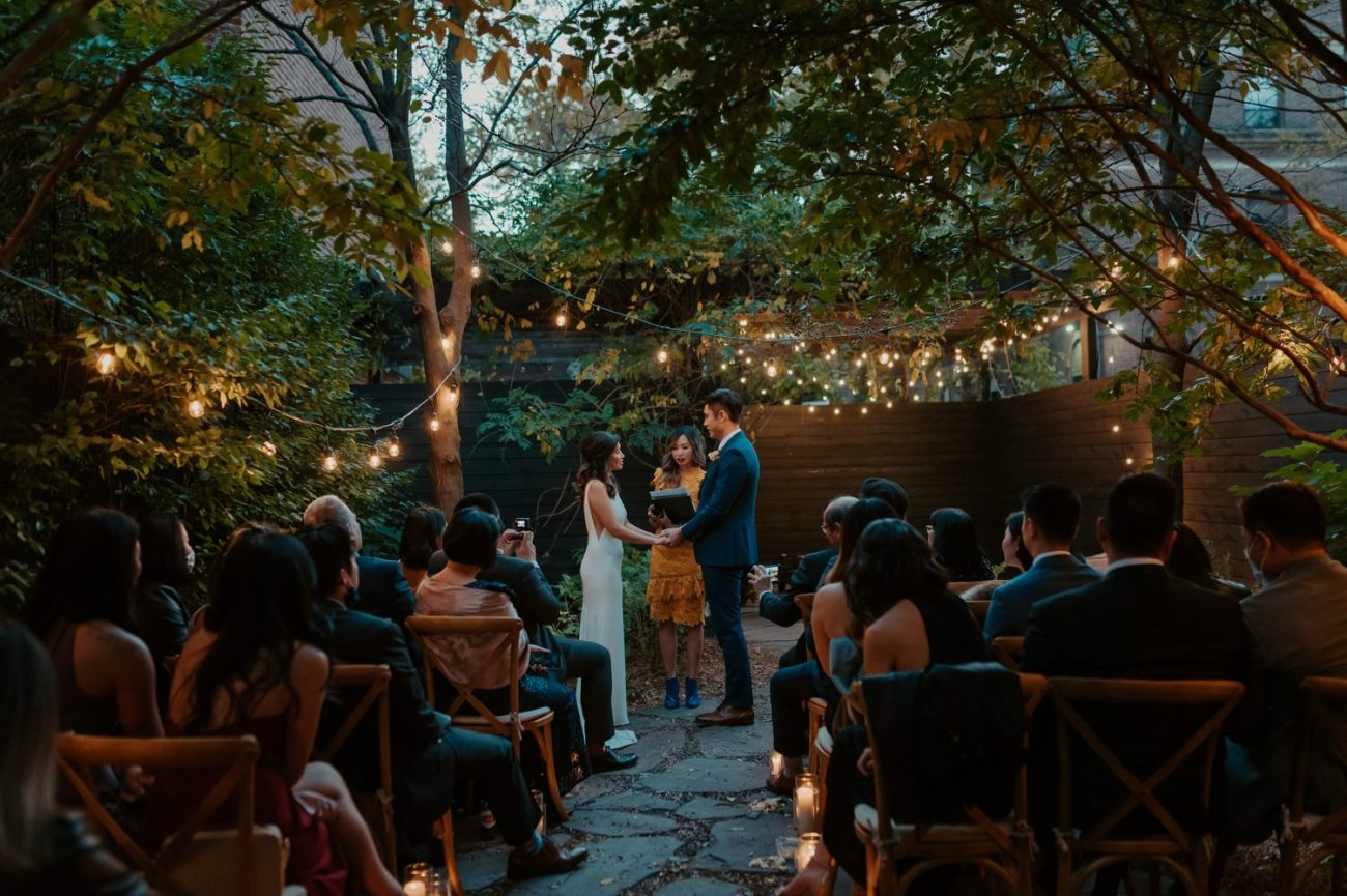 Bride and Groom exchanging vows for their Brownstone Backyard Wedding in Brooklyn. Anais Possamai Photography