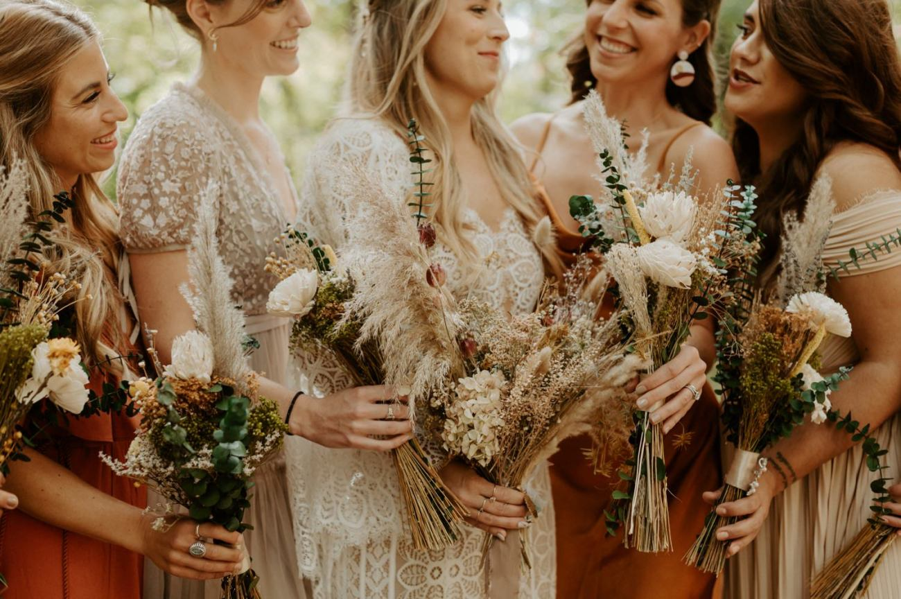 Bride and bridesmaids mismatched neutral, rust orange color palette dresses and dry flower bouquets