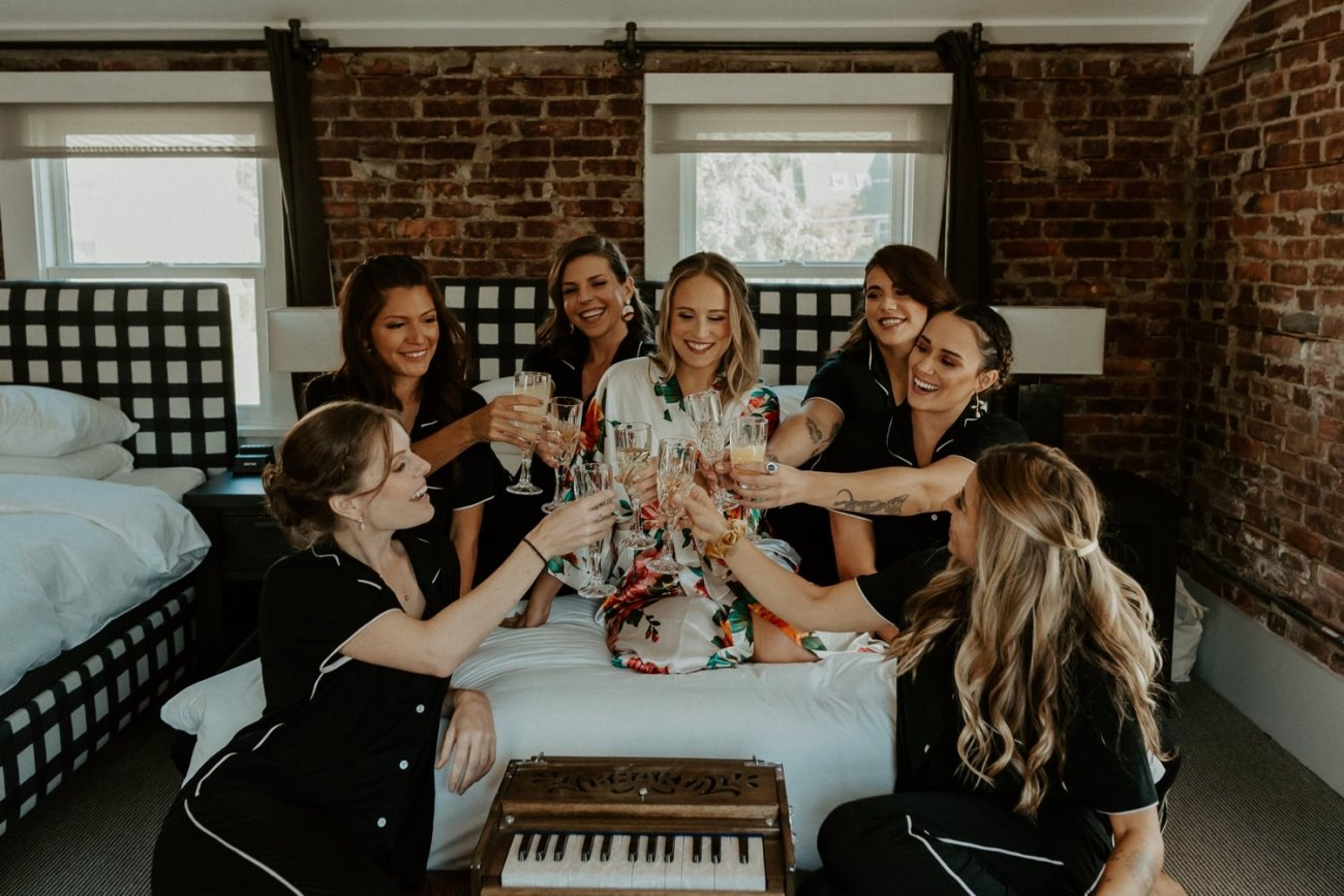 Bride and bridesmaids cheering with champagne in a hotel room
