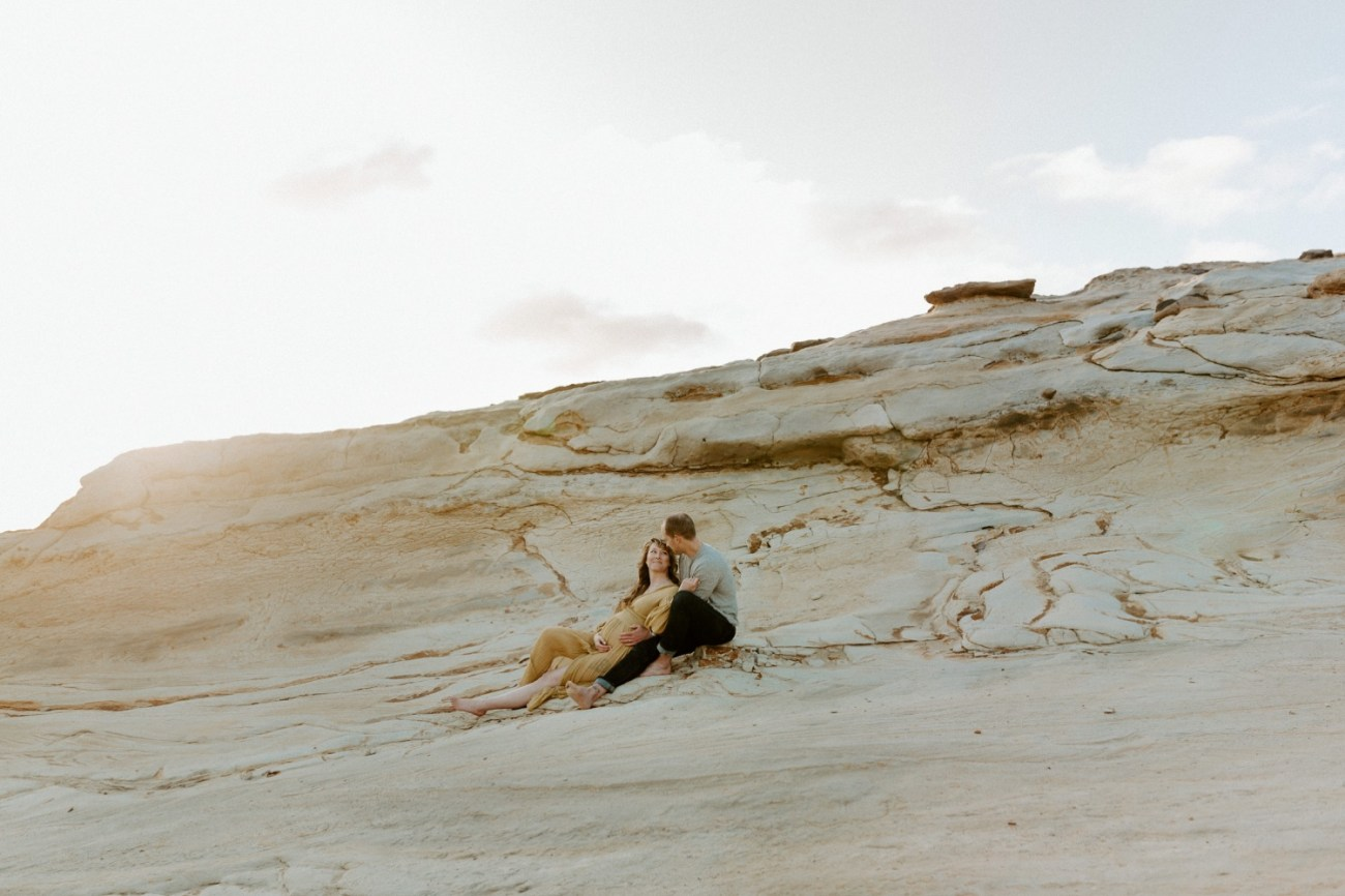 Couple sitting on the dunes in Pacific City Cape Kiwanda Oregon for their maternity session