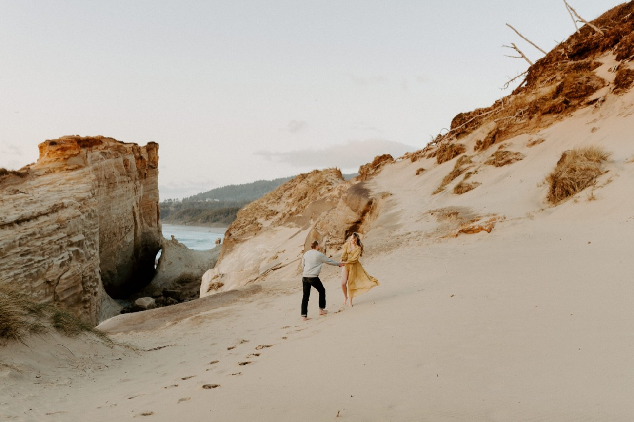 Couple walking on the coast in Pacific City Cape Kiwanda Oregon for their maternity session