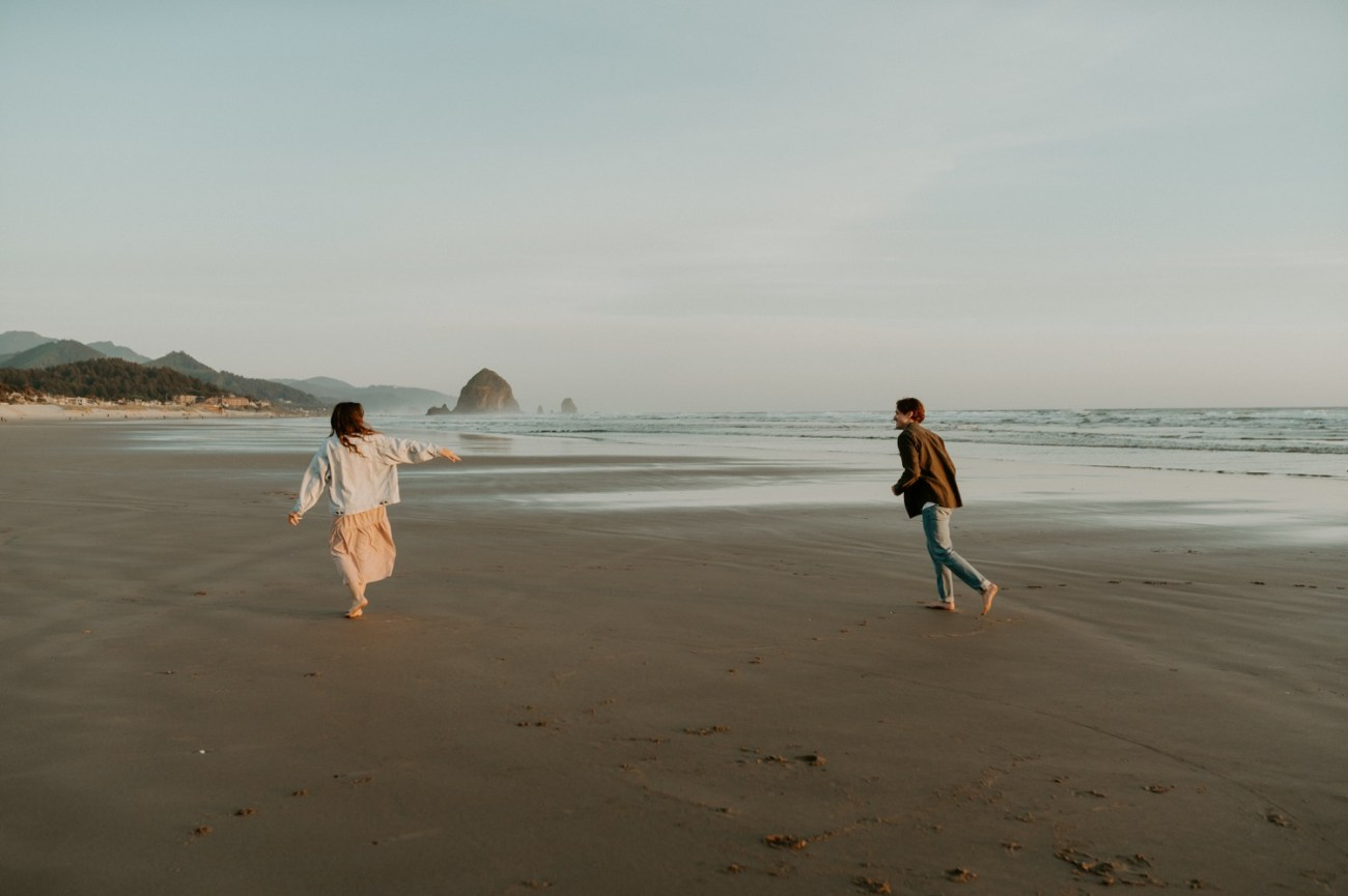Couple running on Cannon Beach for their engagement session