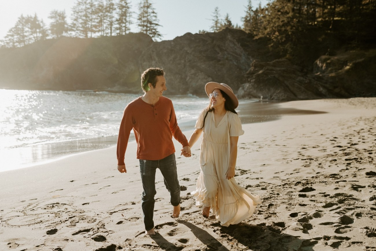 Couple running on Secret Beach in Samuel H Boardman in souther Oregon for their engagement session
