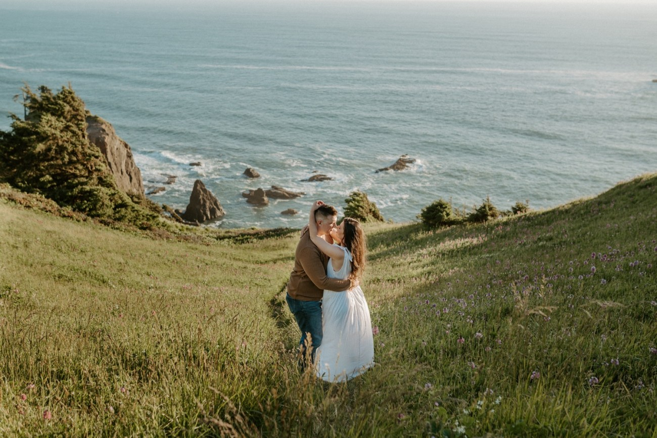 Couple standing by the coastline of God's Thumb for their engagement session