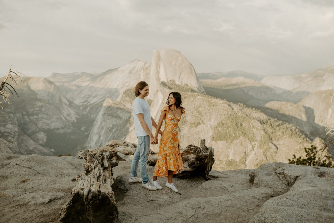 Couple standing at Sunset at Glacier Point View Point for their engagement photos