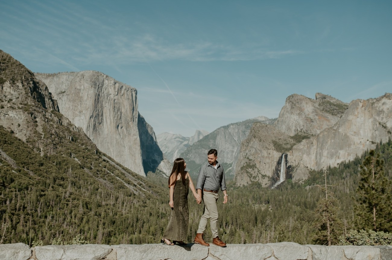 Couple walking on wall at Tunnel View in Yosemite National Park for their engagement photos