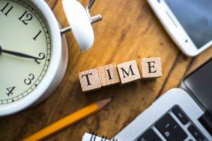 時計、パソコン、スマホ、鉛筆、メモ帳、TIMEと書かれた木片の写真