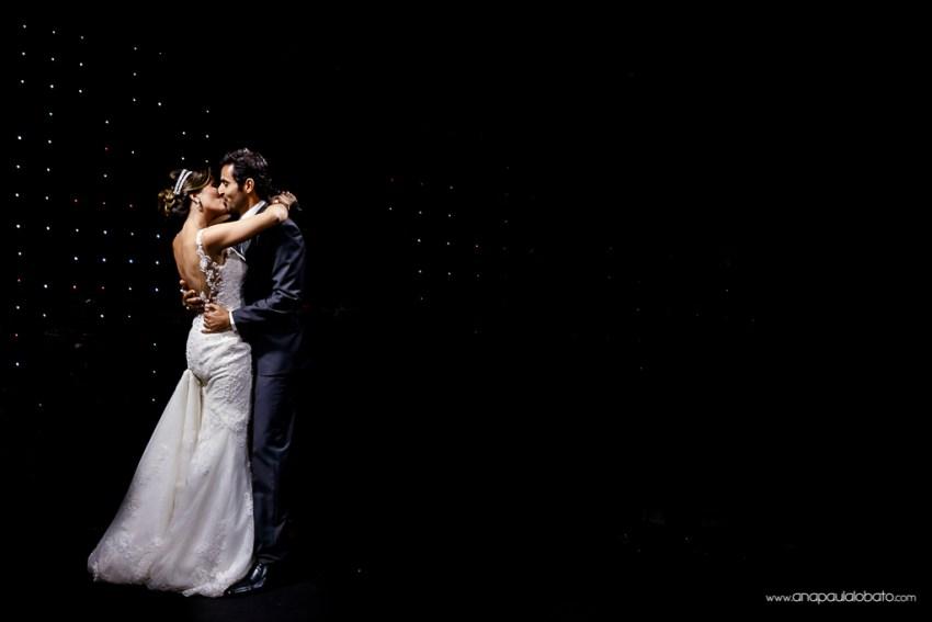 Noivos se beijam no que parece ser um céu estrelado e infinito