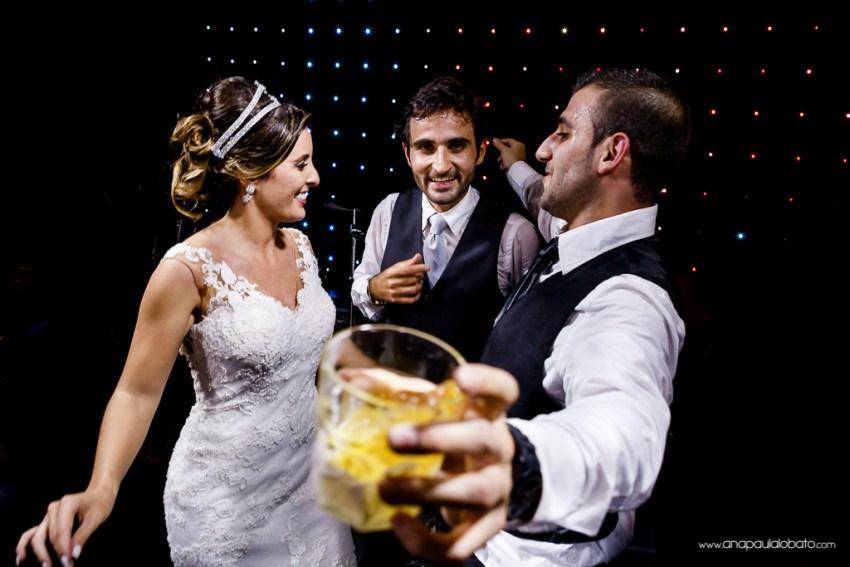 Noivos dançam com padrinho no palco de casamento