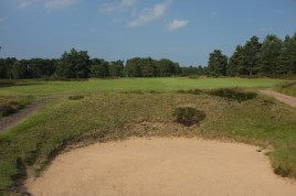 The view from the 9th fairway. The bunker in the foreground is one of three cross bunkers that you must carry with your second shot.