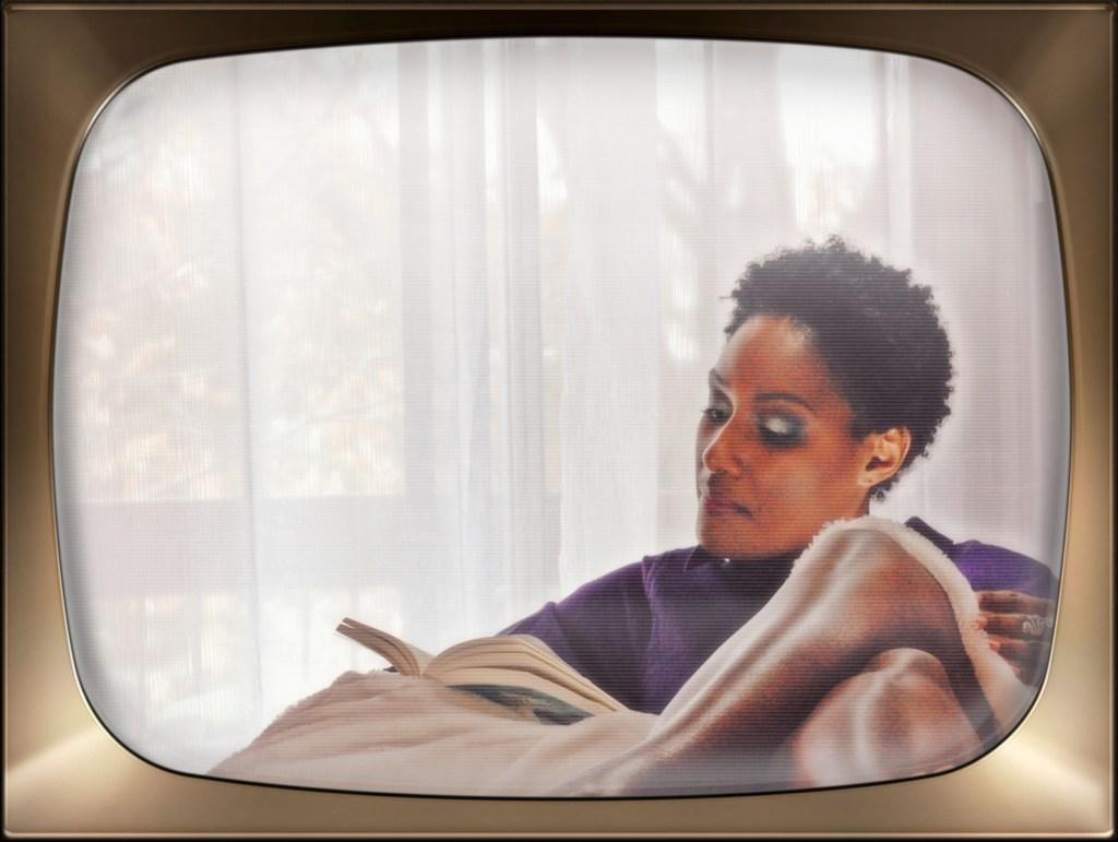 Femme noire assise faisant de la lecture.