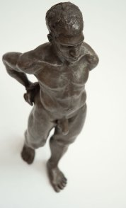 cranial frontal lateral view of bronze sculpture of male nude standing figure