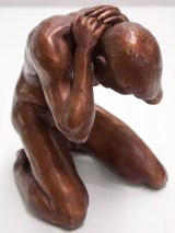 a bronze sculpture of a male nude model sitting on his knees with his hands in his neck, bending a little over