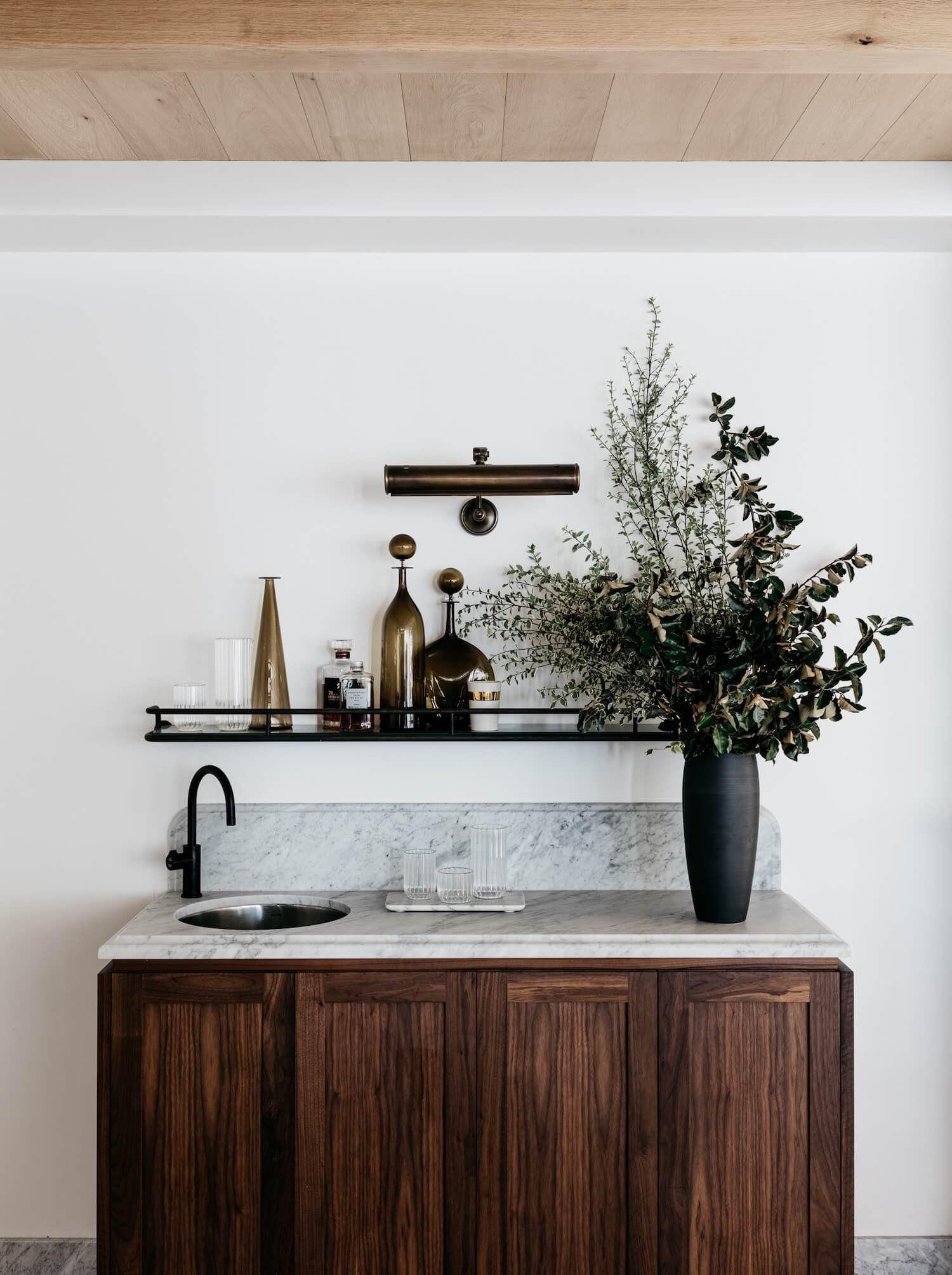 Decoración de interiores acogedor, cálido y sofisticado, mueble bar en madera y lavabo de mármol