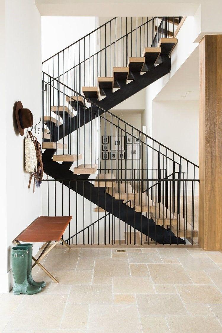 Entrada de vivienda de estilo Farmhouse moderno, escaleras de estructura en hierro negro y madera rústica