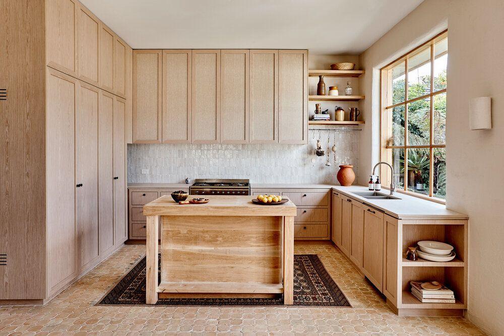 Zona de cocina con isla en madera natural y revestimiento de tadelakt en tonos neutros claros arcilla, sostenible (proyecto del Studio Ezra). @Utrillanais
