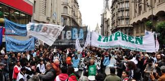 Conglomerado de personas , con banderas de sindicatos de prensa.
