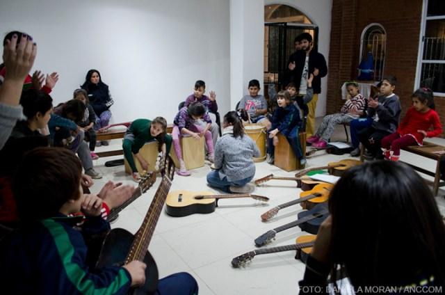 Desde un cuartito del fondo, traen al menos diez guitarras. Los bancos de madera apilados en un rincón enseguida son desarmados y entre todos los acomodan formando una ronda.