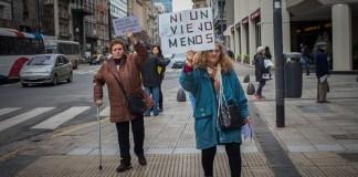 """Dos señoras caminando en la calle y sosteniendo carteles en alto, en uno de ellos se lee: """"ni un viejo menos""""."""