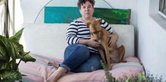La escritora Gabriela Cabezón Cámara está recostada en un sillón de su casa. Tiene la mirada seria puesta en la cámara y con sus brazos rodea a uno de sus perros.