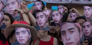 Imagen de personas tapando sus caras con la imagen del rostro de Nahuel Rafael durante la marcha a plaza de mayo para pedir justicia por su asesinato.