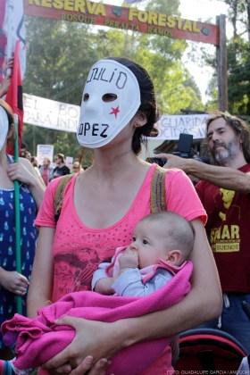 """Mujer con bebé en brazos y una máscara blanca con la inscripción """"Julio López"""" tapando su rostro."""