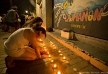 Dos personas prenden velas en la vereda. En la pared más próxima se ve un mural en homenaje a las víctimas de Cromañon.