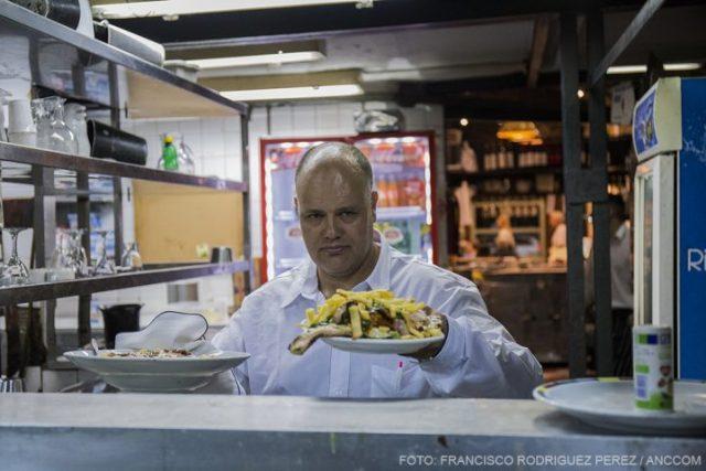 Rosendo, mozo de la Cooperativa Battaglia, lleva platos con comida en el restaurante.