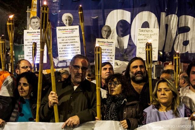 Personas marchando con antorchas, banderas y carteles.