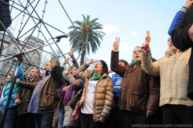 Dirigentes sindicales sobre el escenario levantando sus manos.