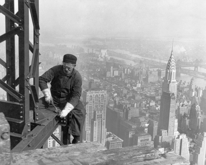 A worker bolts beams during construction; the Chrysler Building can be seen in the background. (Wikipedia)