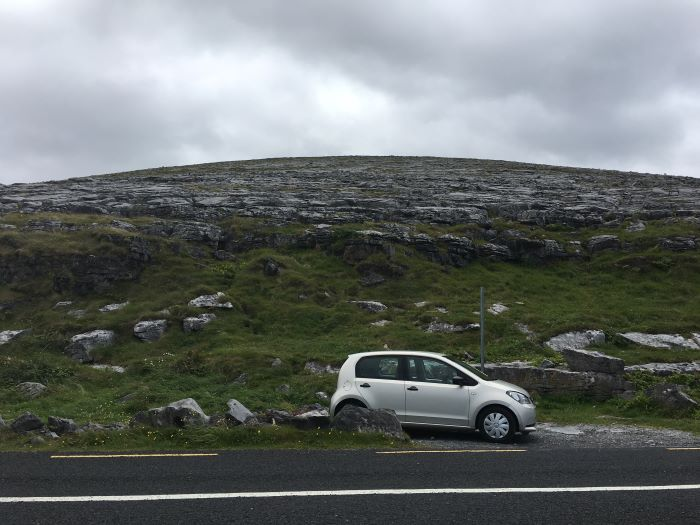 A small car parked on the side of the Wild Atlantic Way. There are cliffs in the background.