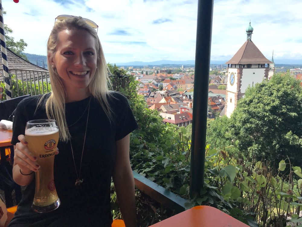 A blonde woman holding a beer in a beer garden in Freiburg. The city is in the distance.