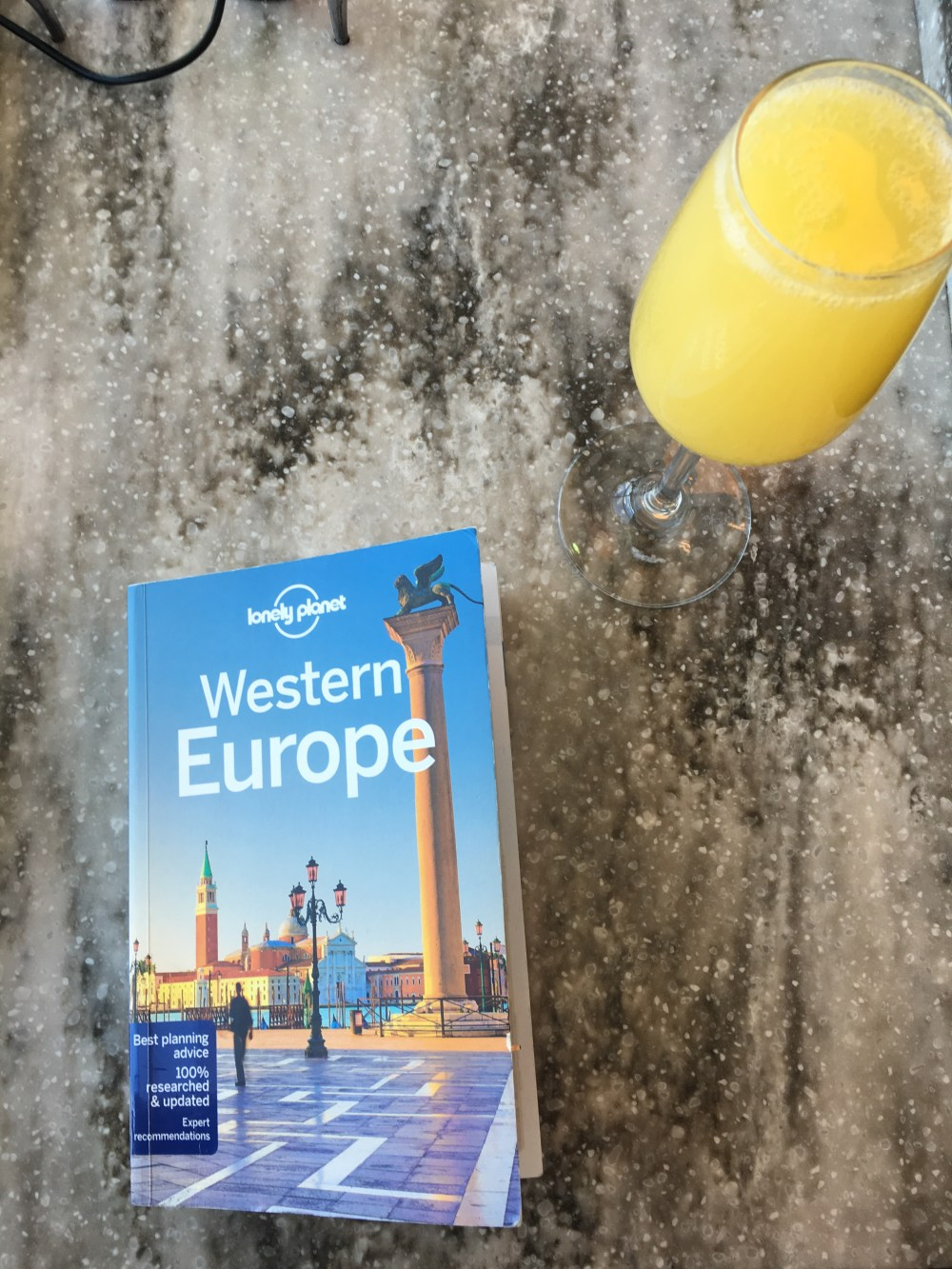 Photo of a Lonely Planet Guidebook cover and a glass of orange juice.
