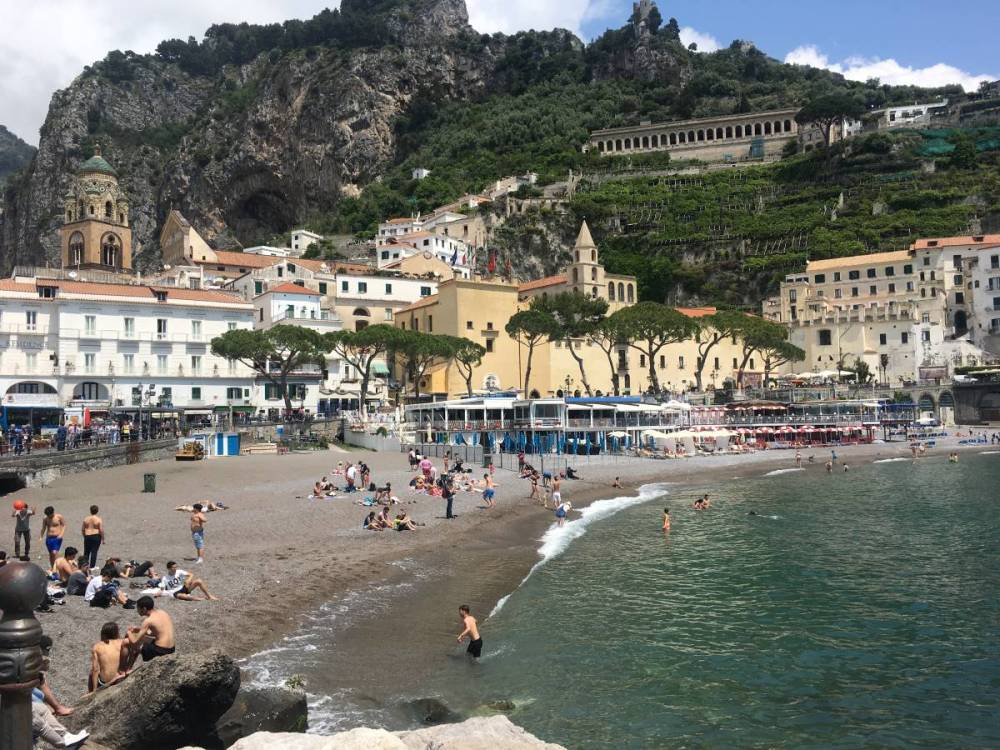 The beach in Amalfi, Italy. There town of Amalfi is in the distance and there are people playing in the ocean.