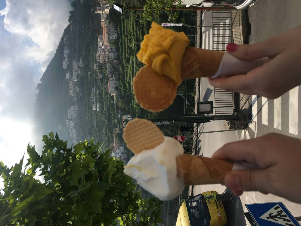 A photo of two hands holding gelato with the hillside town of Scala, Italy, in the distance.