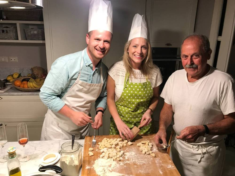 Three people smiling at the camera while cooking pasta during a cooking class in Ravello, Italy.