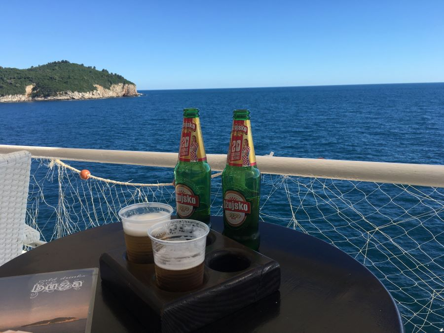 Two beers sitting on a table with the ocean in the background.