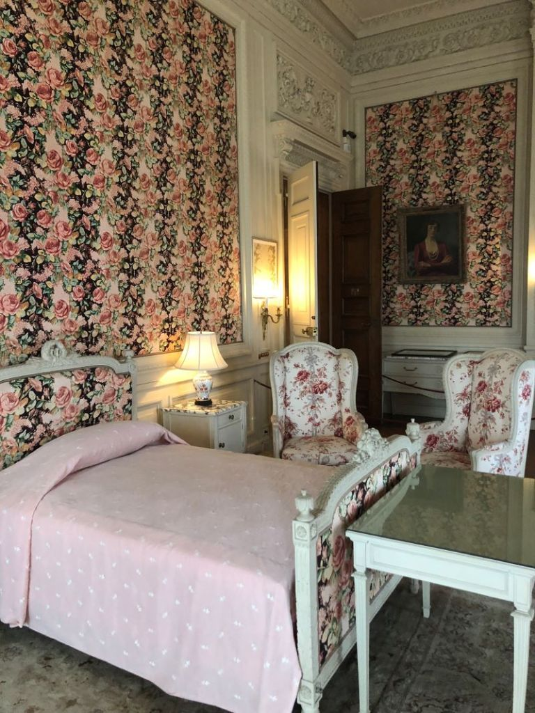 A photo of a bed and two chairs on the Breakers Mansion tour.
