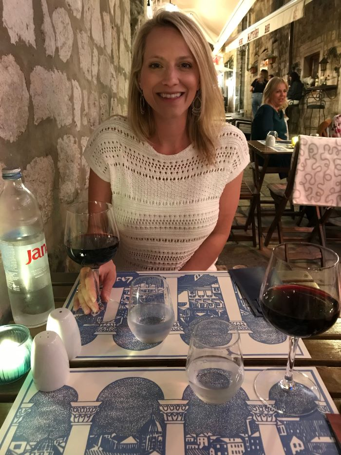 Blonde woman with glass at a restaurant in Dubrovnik.