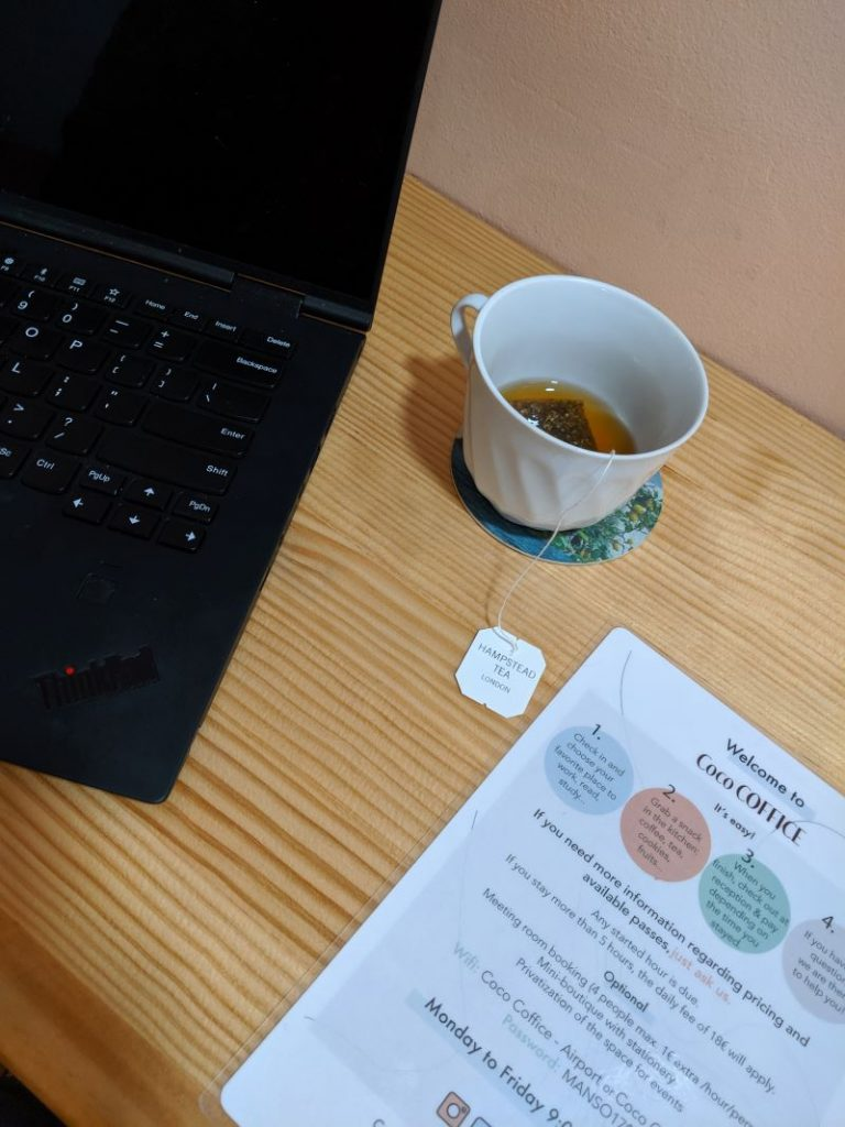 A menu, computer and coffee cup at a coworking space in Barcelona.