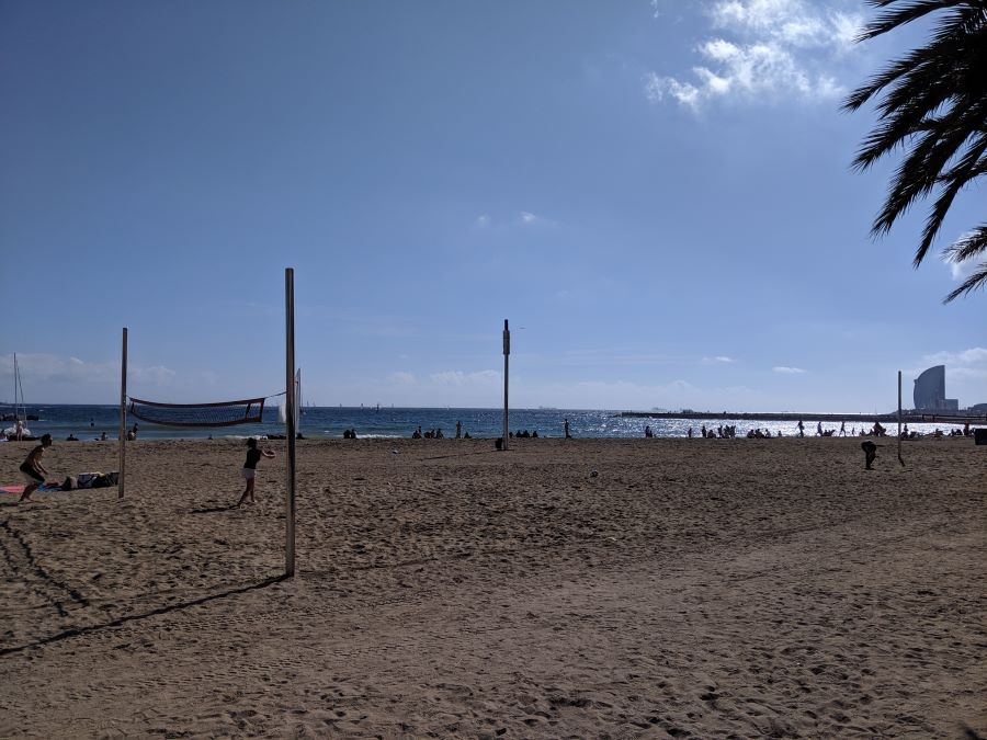 The sandy beaches in Barcelona and two people playing volleyball