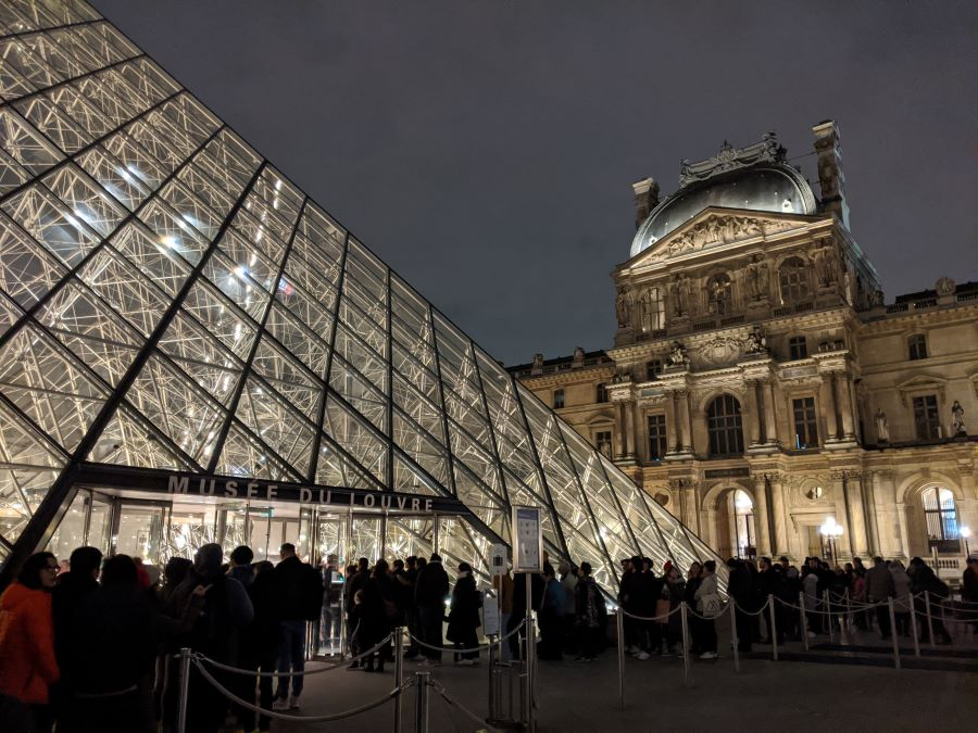 The pyramid dome of the Louvre Museum in Paris lit up in the evening. There is a crowd standing outside waiting to get in the doors.