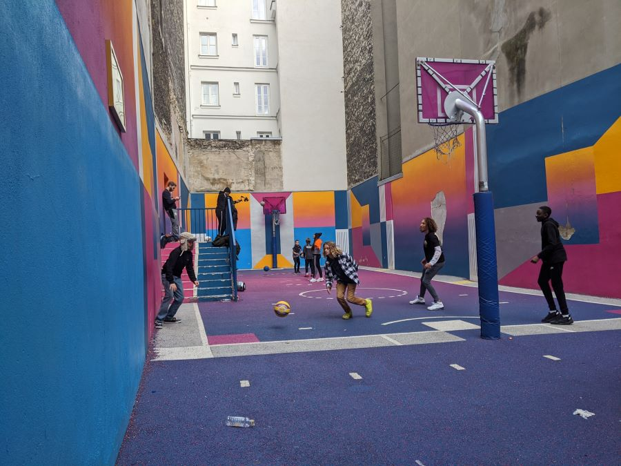 A purple, blue, pink and orange basketball court with several young boys playing a game.