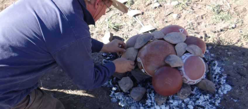 Placing cover sherds on an open fired pottery firing